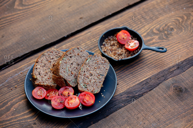Gluten-free bread with pumpkin seeds, tomatoes and salt on wooden table