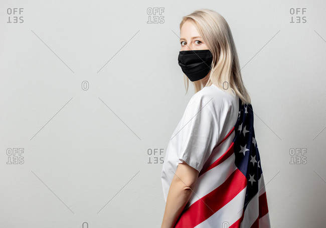 Blonde woman wearing a face mask and a USA flag around her back in front of a white background