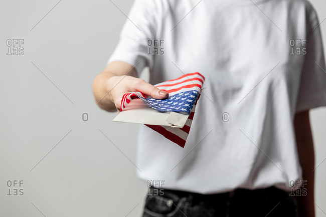 Woman holding an envelope wrapped in an American flag with her vote