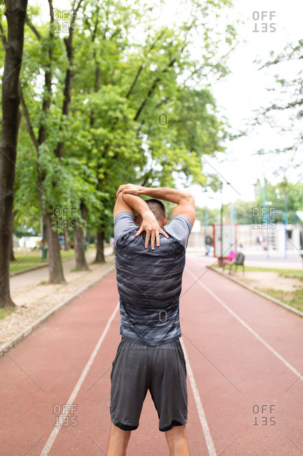 Rear view of man stretching his arms before an outdoor workout