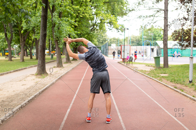 Back view of man stretching before an outdoor workout