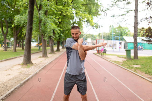 Man stretching his arms before an outdoor workout