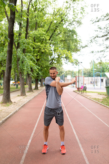 Man on a track stretching his arms before an outdoor workout