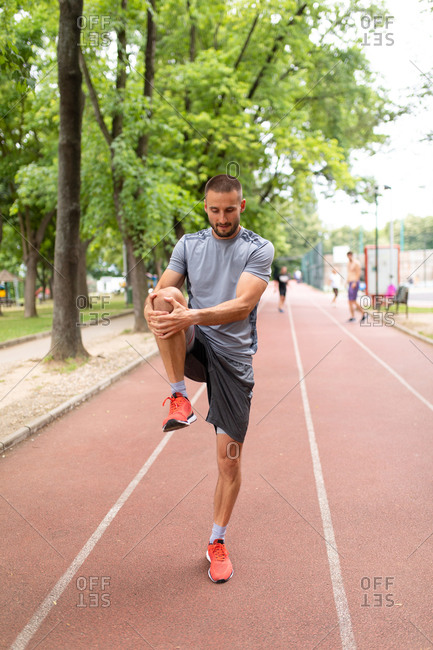 Man on a track stretching his legs before an outdoor workout