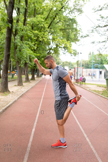 Side view of a man on a track stretching his legs before an outdoor workout