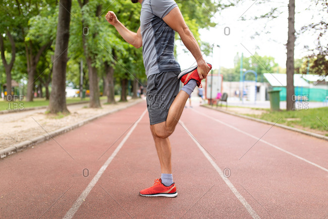 A man on a track stretching his legs before an outdoor workout