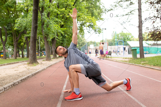 Man doing lunge twist yoga stretch on an outdoor track