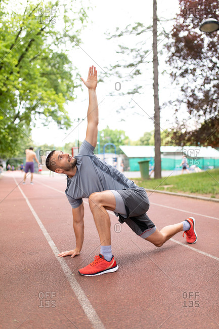 Man doing a twisting lunge yoga stretch on an outdoor track