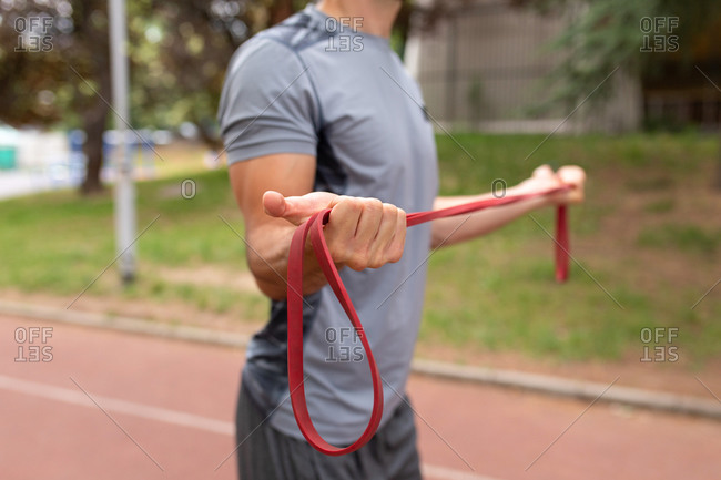 Mid-section of man holding a red resistance band