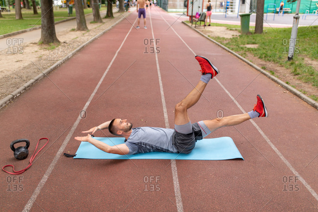 Man doing fitness exercise on an outdoors sports track