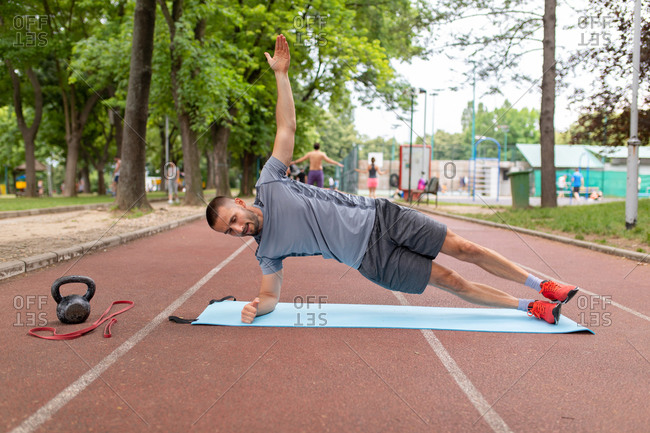 Man practicing a forearm side plank on an outdoor track