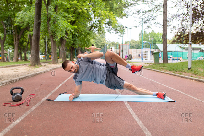 A man doing fitness exercise on an outdoor track