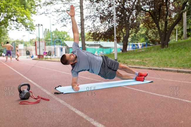 Man looking up at the sky while practicing a forearm side plank on an outdoor track