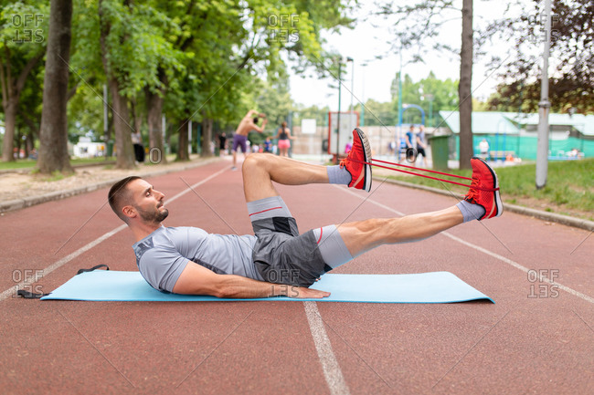 Side view of a man on yoga mat outdoors using a resistance band to workout his legs