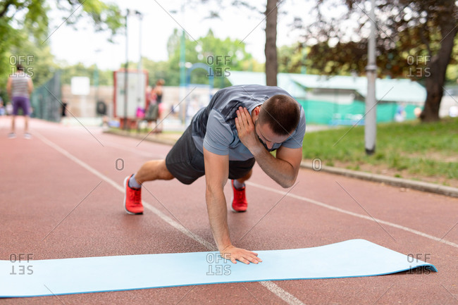 Man doing pushups on a yoga mat on an outdoor track