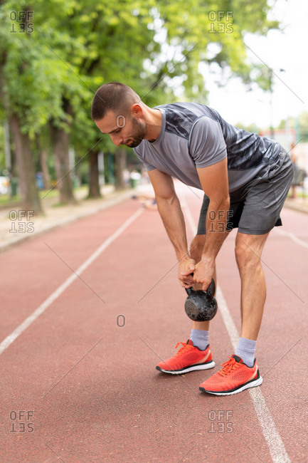 A man training with a kettle bell outdoors