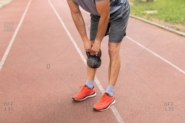 Low-section of a man training with a kettle bell outdoors