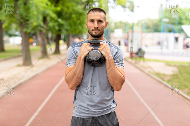 Man holding a kettle bell outdoors on a track