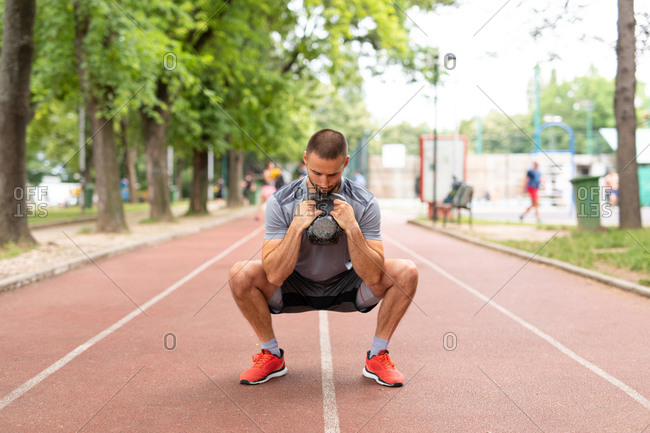 A man squatting while holding a kettle bell outdoors