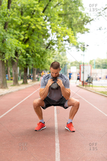 A man squatting while holding a kettle bell on an outdoor track