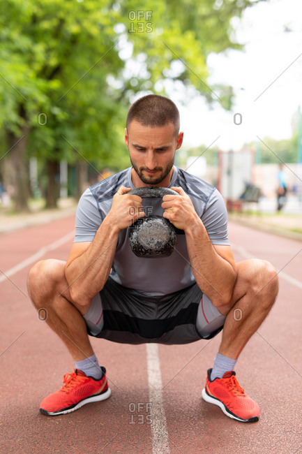 Close up of a man training with a kettle bell outdoors