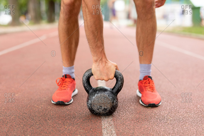 Man with a kettle bell on an outdoor track
