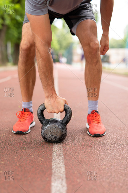 A man with a kettle bell on the ground at an outdoor track