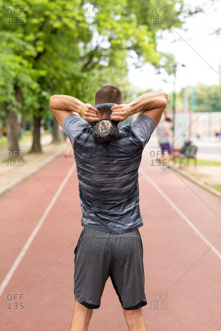 Rear view of a man training with a kettle bell outdoors