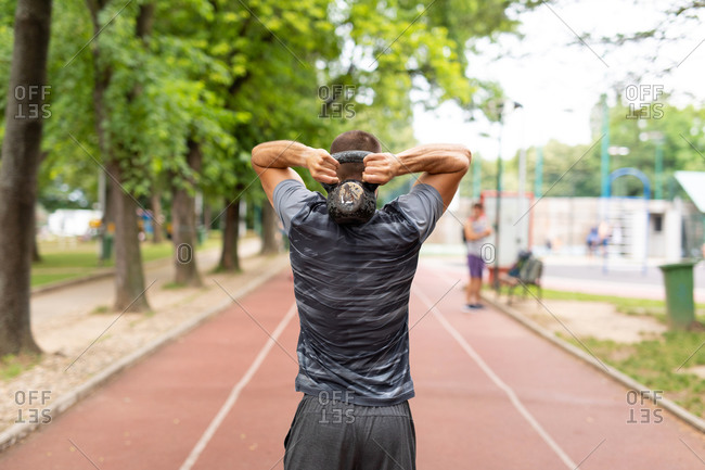 Back view of a man training with a kettle bell outdoors
