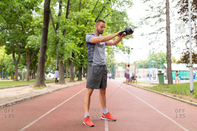 A man swinging a kettle bell forward outdoors
