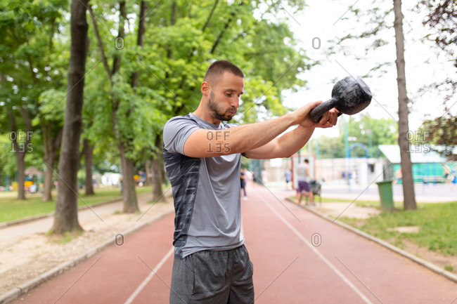 Man breathing heavy while swinging a kettle bell forward outdoors