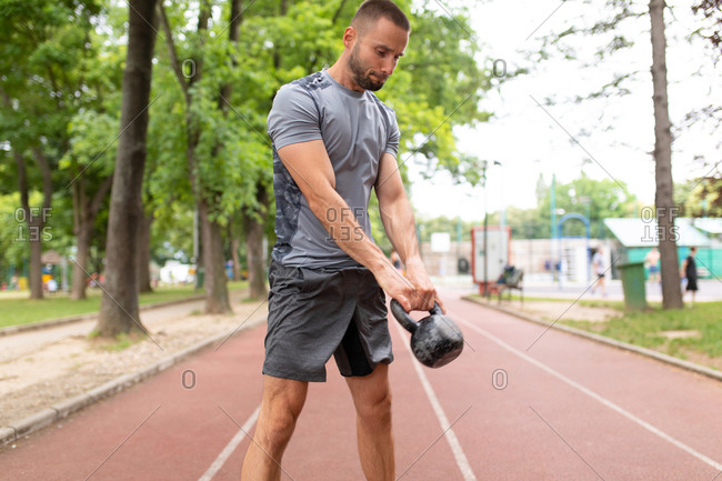 A man training with a kettle bell on an outdoor sports track