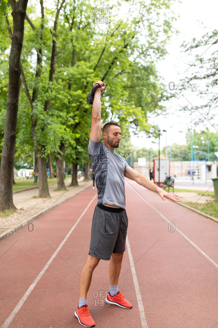 Man lifting a kettle bell in the air on an outdoor sports track