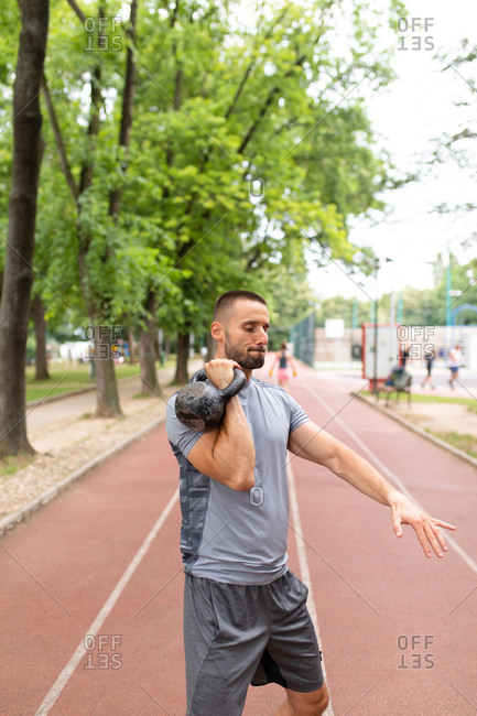 Man lifting a kettle bell on an outdoor sports track