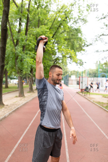 A man lifting a kettle bell in the air on an outdoor track