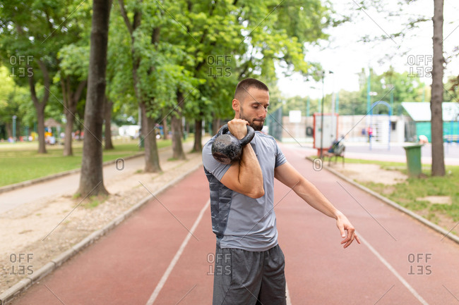 Man lifting a kettle bell weight on an outdoor track