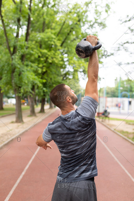 Rear view of man lifting a kettle bell in the air outdoors
