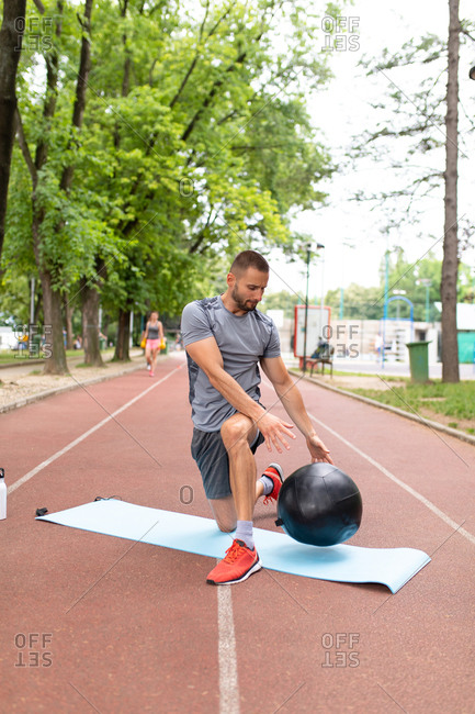 A man training with a medicine ball on a sports track