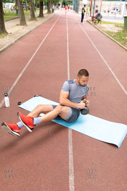 Man sitting on yoga mat training with a kettle bell outdoors