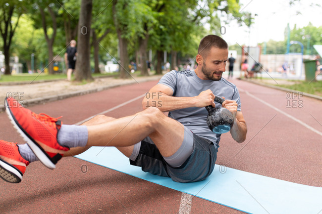 Man sitting on yoga mat training with a kettle bell at an outdoor sports track