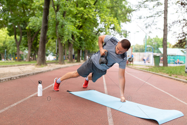 A man doing a workout with a kettle bell outdoors