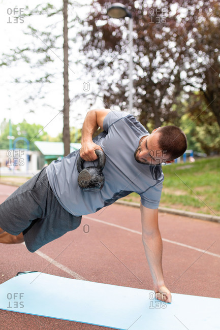 Man doing a workout with a kettle bell outdoors