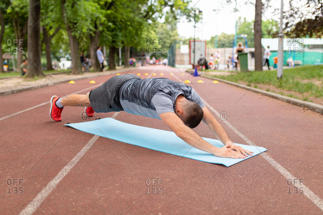 Man doing pushups during workout on a sports track
