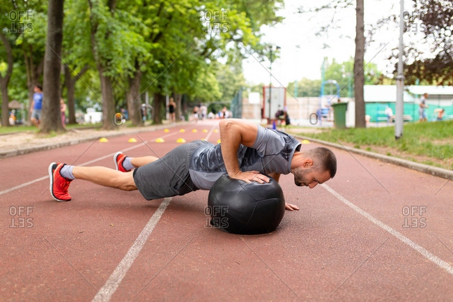 Sportive man doing pushups with a medicine ball during workout on a sports track