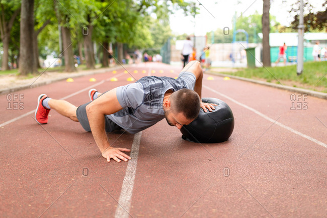 Man doing pushups with a medicine ball during workout on a sports track