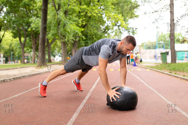 Sportive man using a medicine ball to do pushups during workout outdoors