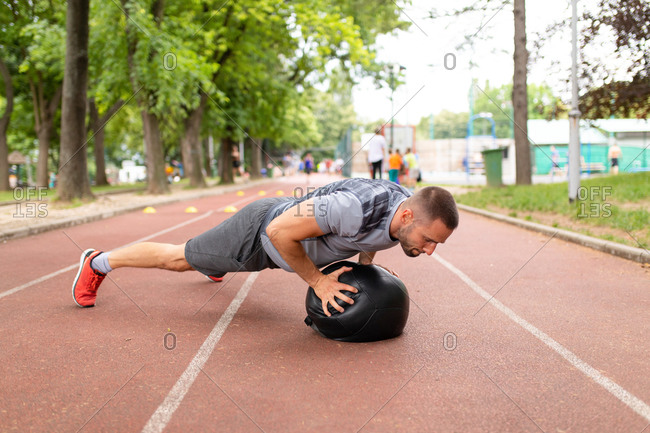 Man using a medicine ball to do pushups during workout on a sports track