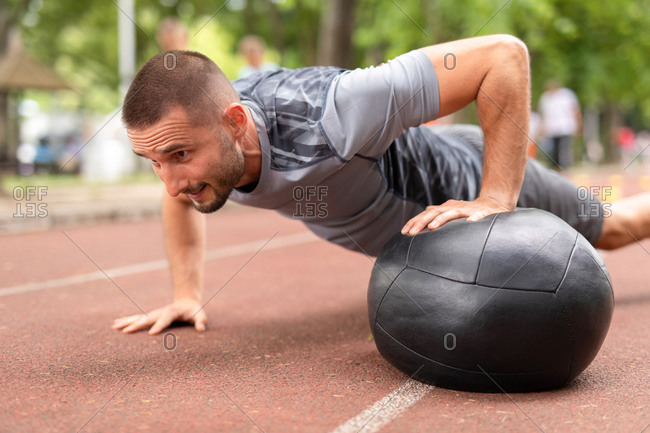 Close up of a man using a medicine ball to do pushups during workout on a sports track