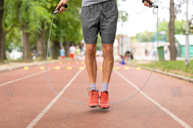 Man jumping rope while working out on a sports track