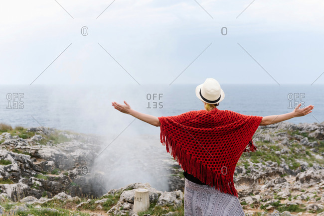Back view of unrecognizable female tourist in red knitted poncho and hat standing on rocky coast near geyser and admiring nature while visiting Jesters of Arenillas in Llanes in Spain